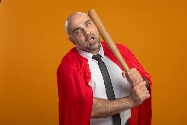 Super hero businessman in red cape punching himself with baseball bat