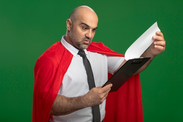 Super hero businessman in red cape showing clipboard with blank pages looking at it intrigued standing over green wall