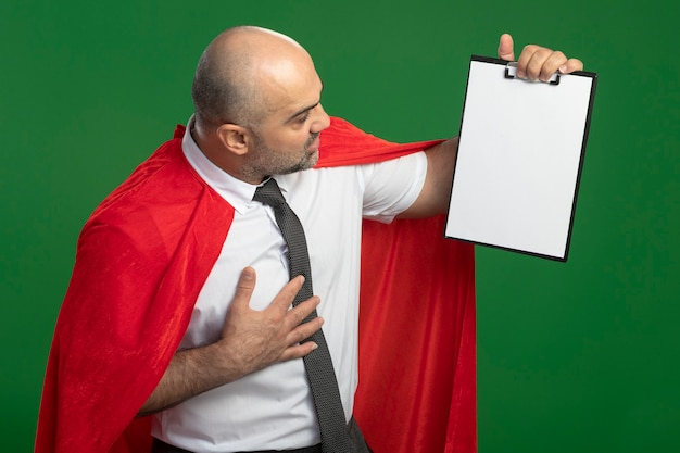 Super hero businessman in red cape showing clipboard with blank pages looking at it intrigued