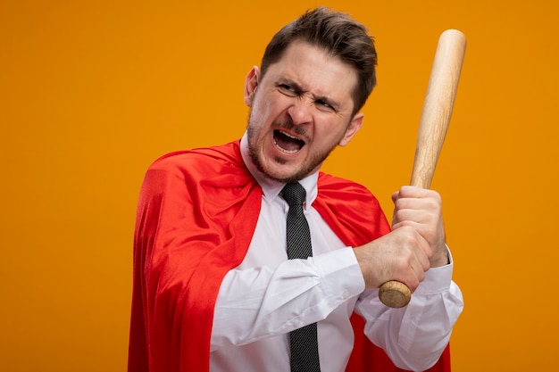 Super hero businessman in red cape swinging baseball bat shouting with aggressive expression standing over orange background