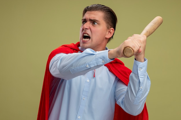 Super hero businessman in red cape swinging baseball bat with aggressive expression standing over light background