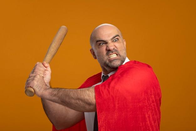 Uomo d'affari super eroe in mantello rosso oscillante mazza da baseball con espressione aggressiva arrabbiata che diventa selvaggia