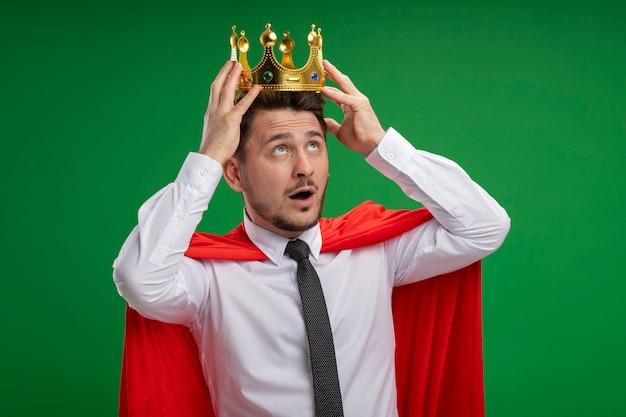 Uomo d'affari super eroe in mantello rosso che tocca la sua corona sulla sua testa essendo confuso in piedi sopra il muro verde