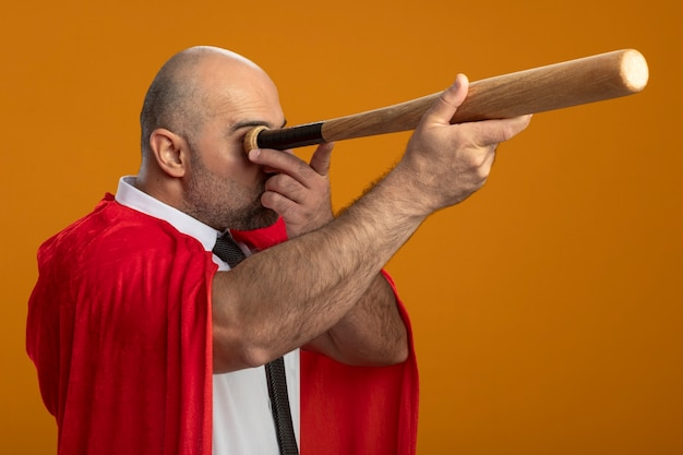 Super hero businessman in red cape using baseball bat like spyglass standing over orange wall