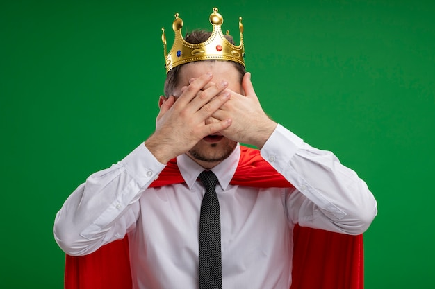 Super hero businessman in red cape wearing crown covering eyes with hands standing over green background