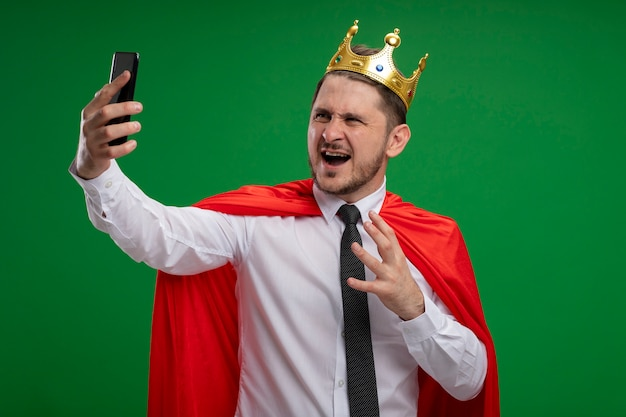 Super hero businessman in red cape wearing crown doing selfie using smartphone going wild crazy angry standing over green background