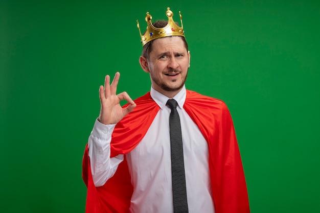 Super eroe uomo d'affari in mantello rosso che indossa corona lookign sorridente che mostra segno giusto in piedi sopra la parete verde
