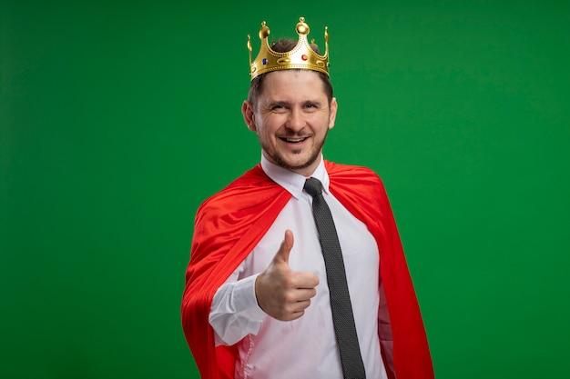 Uomo d'affari super eroe in mantello rosso che indossa lookign corona sorridente con la faccia felice che mostra i pollici in su in piedi sopra la parete verde