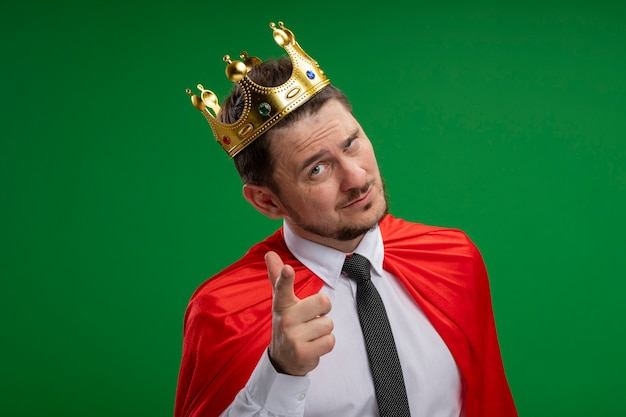 Super hero businessman in red cape wearing crown looking at camera looking at camera smiling confident poiniting with index figner at camera standing over green background