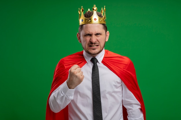 Super hero businessman in red cape wearing crown looking at camera with angry face clenching fist standing over green background