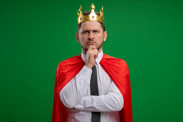 Super hero businessman in red cape wearing crown looking at camera with hand on chin with confident serious expression thinking standing over green background