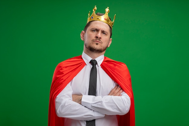 Super hero businessman in red cape wearing crown looking at camera with serious confident expression woth crossed arms on chest standing over green background