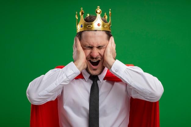 Uomo d'affari supereroe in mantello rosso che indossa la corona che grida essendo frustrato con le mani sul viso con gli occhi chiusi in piedi sopra la parete verde
