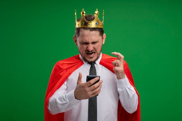 Super hero businessman in red cape wearing crown using smartphone going wild crazy angry standing over green background