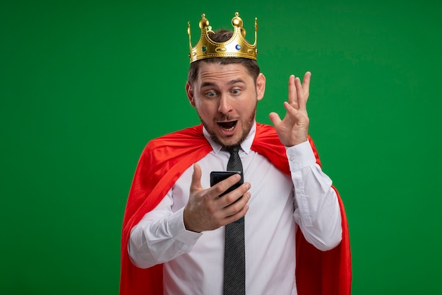Super hero businessman in red cape wearing crown using smartphone looking amazed and surprised standing over green background