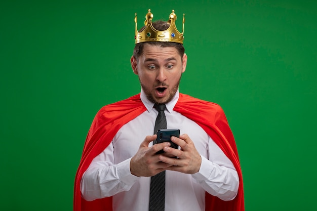 Super hero businessman in red cape wearing crown using smartphone looking amazed and surprised standing over green wall