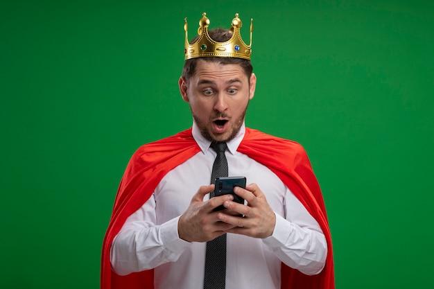 Uomo d'affari super eroe in mantello rosso che indossa la corona utilizzando smartphone guardando stupito e sorpreso in piedi sopra la parete verde