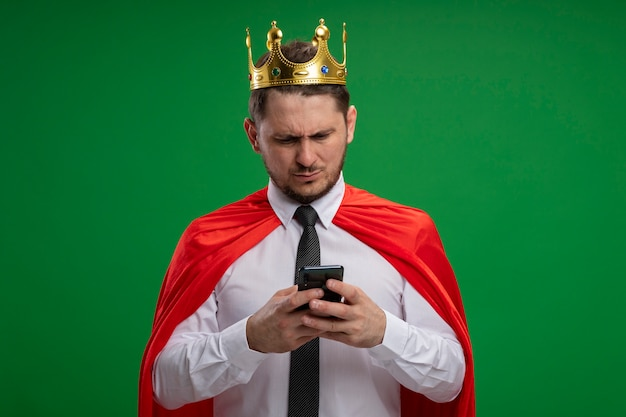Super hero businessman in red cape wearing crown using smartphone looking at it with serious face standing over green background