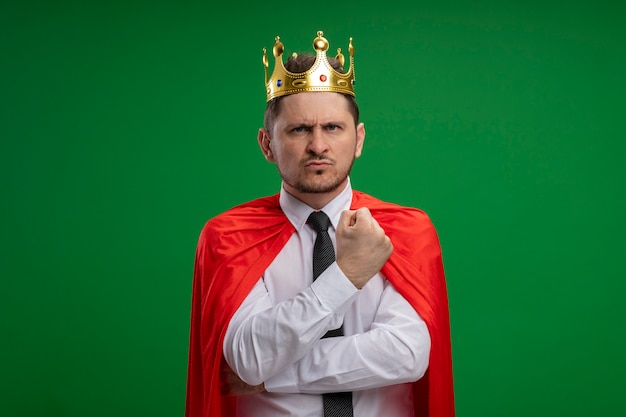 Super hero businessman in red cape wearing crown  with serious face being displeased standing over green wall