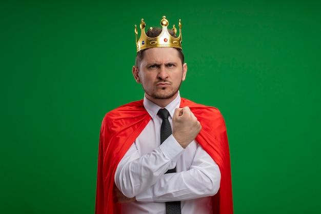 Uomo d'affari super eroe in mantello rosso che indossa la corona con la faccia seria dispiaciuto in piedi sopra la parete verde