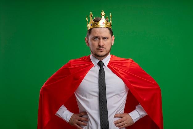 Uomo d'affari super eroe in mantello rosso che indossa la corona con la faccia seria con le braccia all'anca in piedi sopra la parete verde