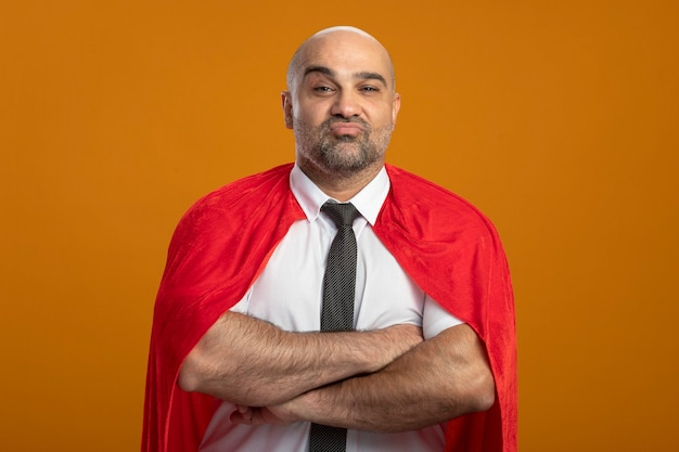 Uomo d'affari super eroe in mantello rosso con espressione fiduciosa con le braccia incrociate sul petto