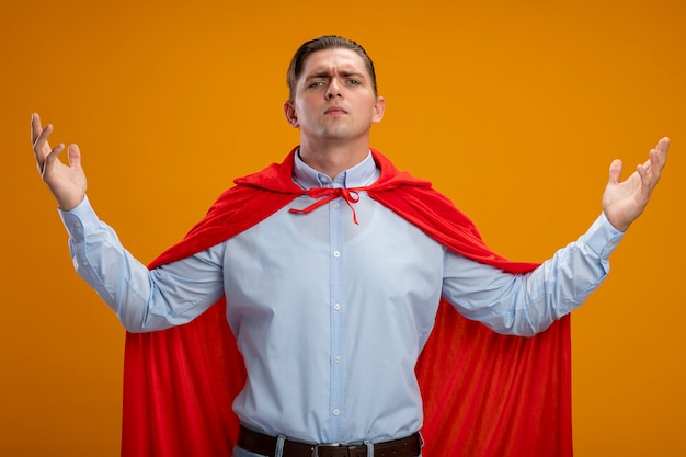 Super hero businessman in red cape  with raised arms being confident and proud standing over orange wall
