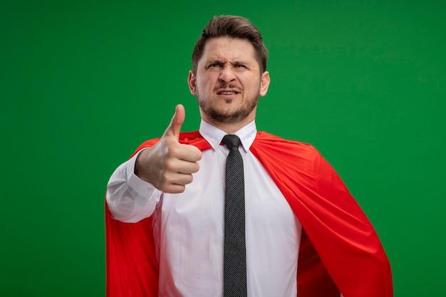 Uomo d'affari super eroe in mantello rosso con la faccia seria che mostra i pollici in su in piedi sopra la parete verde