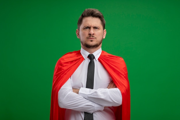 Super hero businessman in red cape  with serious face with crossed arms on chest standing over green wall