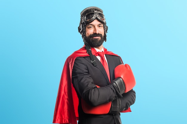 Super hero businessman with boxing gloves on colorful background