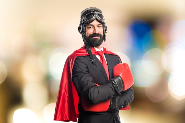 Super hero businessman with boxing gloves on unfocused background
