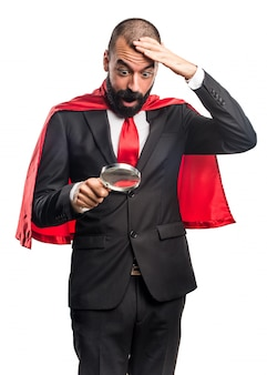 Super hero businessman with magnifying glass