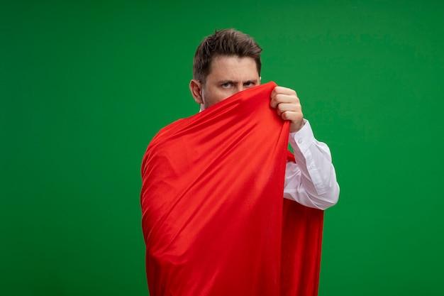 緑の背景の上に立っている真面目な顔でカメラを見て赤いマントに包まれたスーパーヒーローの実業家
