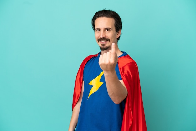 Super hero caucasian man isolated on blue background doing coming gesture