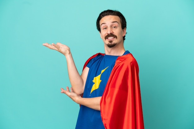 Super hero caucasian man isolated on blue background extending hands to the side for inviting to come