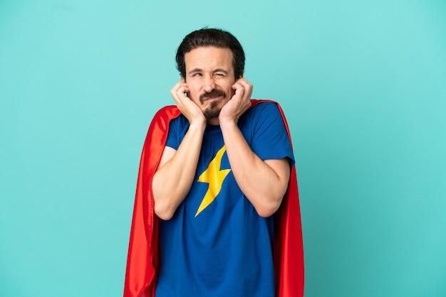 Кавказский человек супергероя изолирован на синем фоне разочарован и закрывает уши