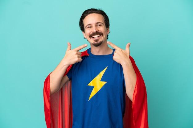 제스처를 엄지손가락을 포기 하는 파란색 배경에 고립 된 슈퍼 영웅 백인 남자