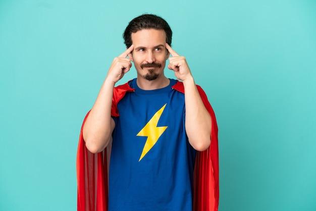 Кавказский человек супергероя изолирован на синем фоне, сомневаясь и думая