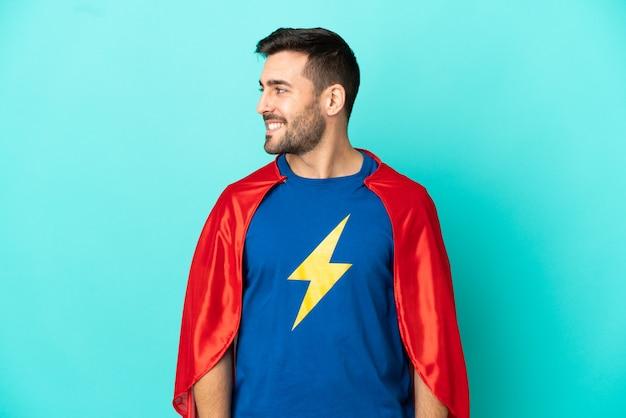Кавказский человек супергероя изолирован на синем фоне, глядя в сторону
