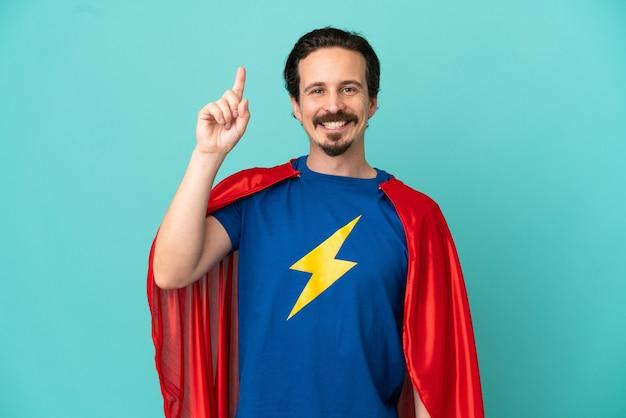 素晴らしいアイデアを指している青い背景に分離されたスーパーヒーロー白人男性