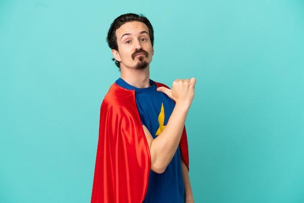 Кавказский человек супергероя изолирован на синем фоне, гордый и самодовольный