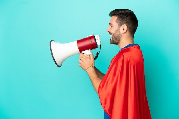 Кавказский человек супергероя изолирован на синем фоне и кричит в мегафон