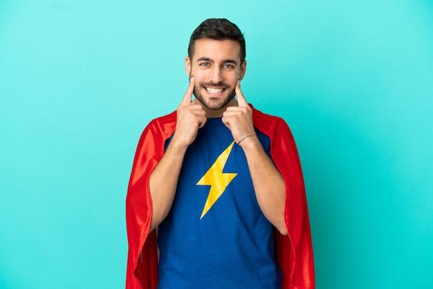 幸せで楽しい表情で笑顔の青い背景に分離されたスーパーヒーロー白人男性
