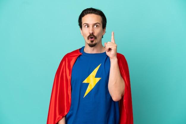 Кавказский человек супергероя изолирован на синем фоне, думая об идее, указывая пальцем вверх