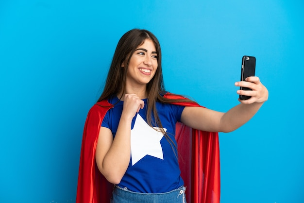 Super hero caucasian woman isolated on blue background making a selfie