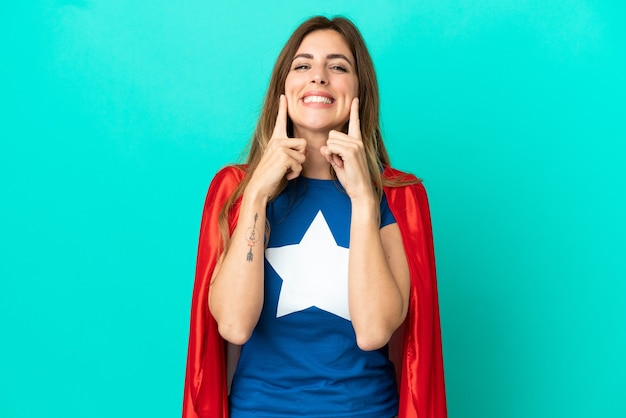 Super hero caucasian woman isolated on blue wall smiling with a happy and pleasant expression