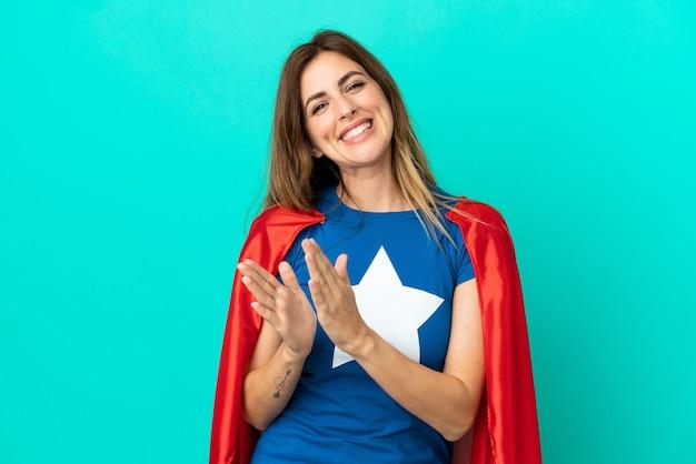Кавказская женщина супергероя изолирована на синем фоне аплодирует после презентации на конференции