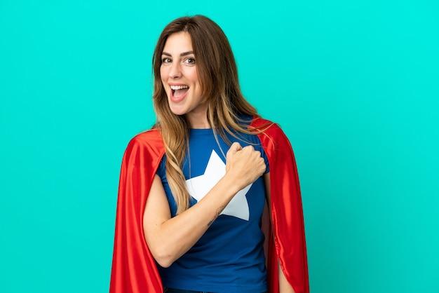 Кавказская женщина супергероя изолирована на синем фоне празднует победу