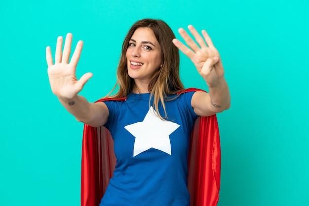 Кавказская женщина супергероя изолирована на синем фоне, считая девять пальцами