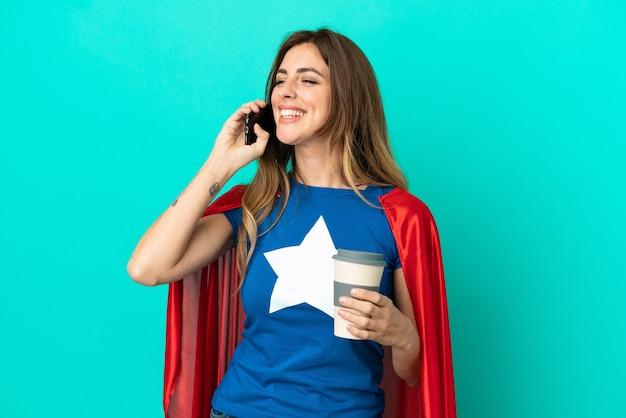 파란색 배경에 격리된 슈퍼 히어로 백인 여성은 커피를 들고 휴대전화를 들고 있습니다.